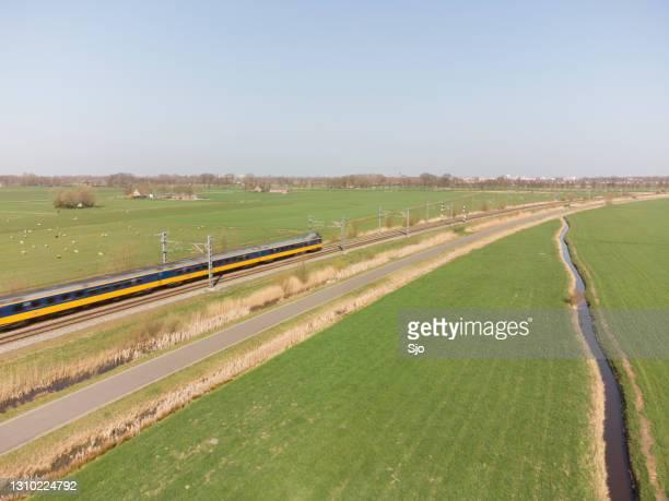 "train of the nederlandse spoorwegen (ns) driving through a rural landscape during springtime - ""sjoerd van der wal"" or ""sjo"" stock pictures, royalty-free photos & images"