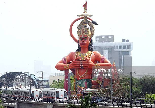 A train of the New Delhi Metro passes by a new temple dedicated to and made in a likeness of Lord Hanuman the monkey god of Hindu mythology in New...