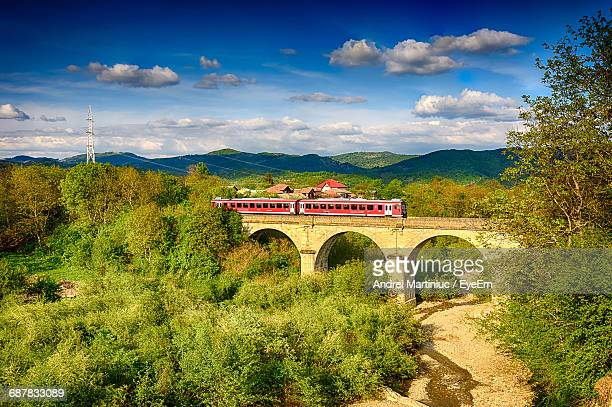 train on arch bridge by mountains against sky - rumania fotografías e imágenes de stock