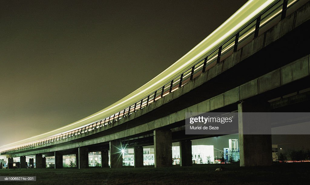 Train on elevated railroad track, blurred motion, night : Foto stock