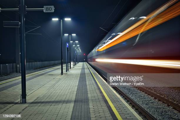train on railroad station platform at night - rail transportation stock pictures, royalty-free photos & images