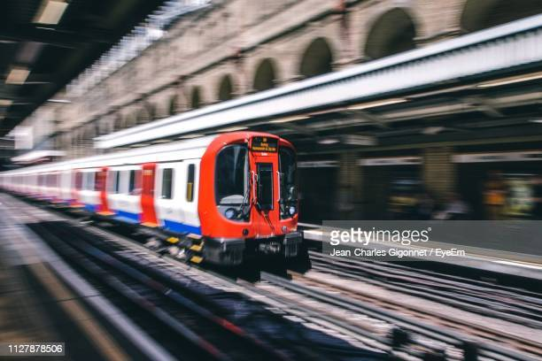 train on railroad station platform - red tube stock photos and pictures