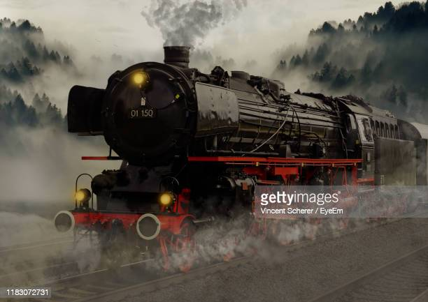 train on railroad track against sky - steam train stock pictures, royalty-free photos & images
