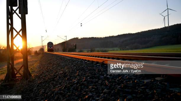 train on railroad tracks against sky during sunset - bahngleis stock-fotos und bilder