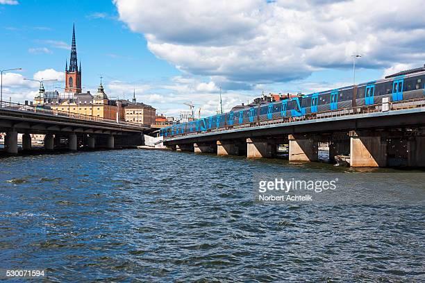 train on railway bridge in city, gamla stan, stockholm, sweden - riddarholmkirche stock-fotos und bilder