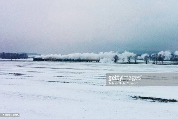 Train On Snow Covered Landscape Against Clear Sky