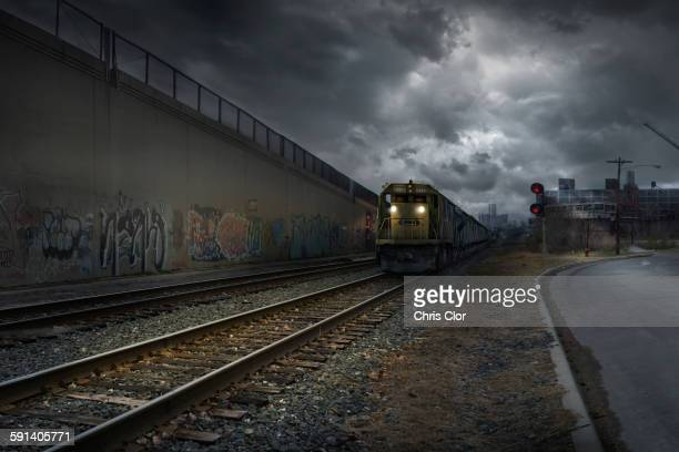 train on train tracks in dilapidated industrial city - train graffiti stock photos and pictures