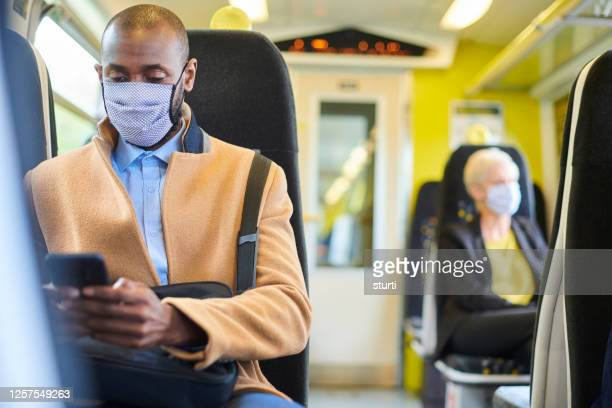 train passenger with homemade mask texting - commuter stock pictures, royalty-free photos & images