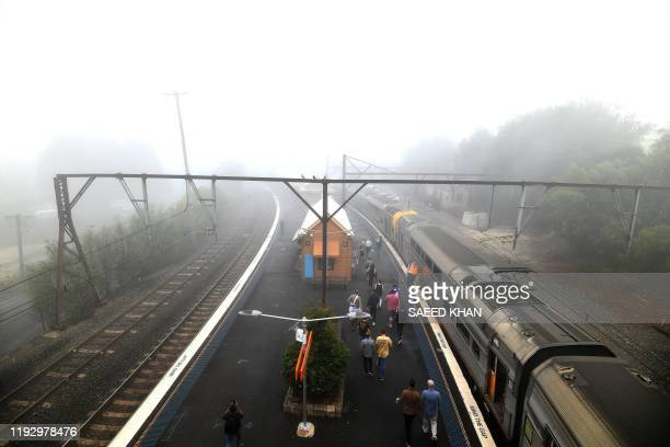Train passengers alight at the Katoomba railway station as fog mixed with bushfire smoke fills the sky in the Blue Mountains some 75 kilometres from...