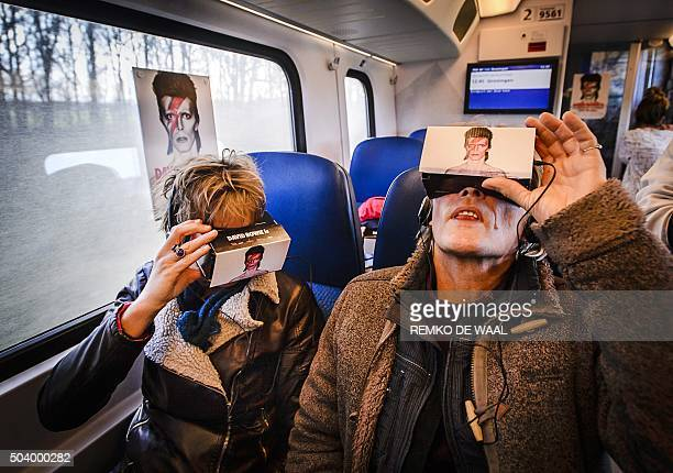 TOPSHOT Train passengers take a virtual reality journey through the life of the British pop star David Bowie which is exhibited in a 'Virtual Bowie...