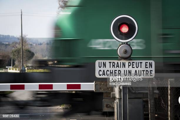 A train passes by a grade crossing bearing a sign reading One train can hide another near the city of Montlaur near Toulouse southern France on March...