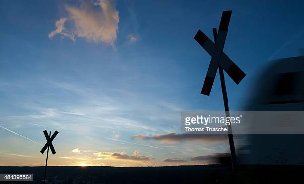 A train passes by a level crossing during sunrise on October 29 2010 in Martinroda Germany