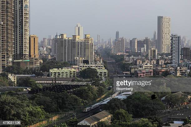 A train passes commercial and residential buildings in Mumbai India on Monday May 11 2015 Mumbai's longcherished dream of becoming another Shanghai...