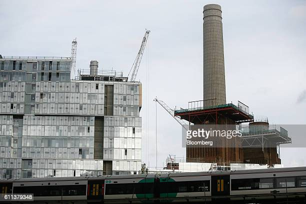 A train passes ongoing construction work at the Battersea Power Station office retail and residential development which is backed by Sime Darby Bhd...