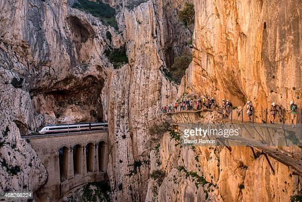 A train passes through a tunnel as tourists walk along the 'El Caminito del Rey' footpath on April 1 2015 in Malaga Spain 'El Caminito del Rey' which...