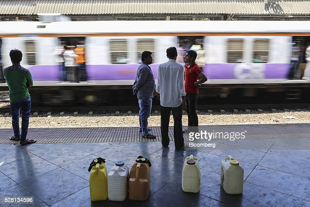 Train passes water commuters standing next to water cans on a platform at Diva railway station in Mumbai, India, on Sunday, April 17, 2016. Hundreds...