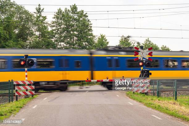 train passing by a railway crossing - crossing sign stock pictures, royalty-free photos & images