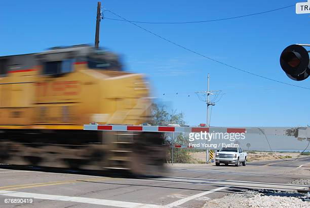 train passing by railroad crossing against clear blue sky - railroad crossing stock pictures, royalty-free photos & images