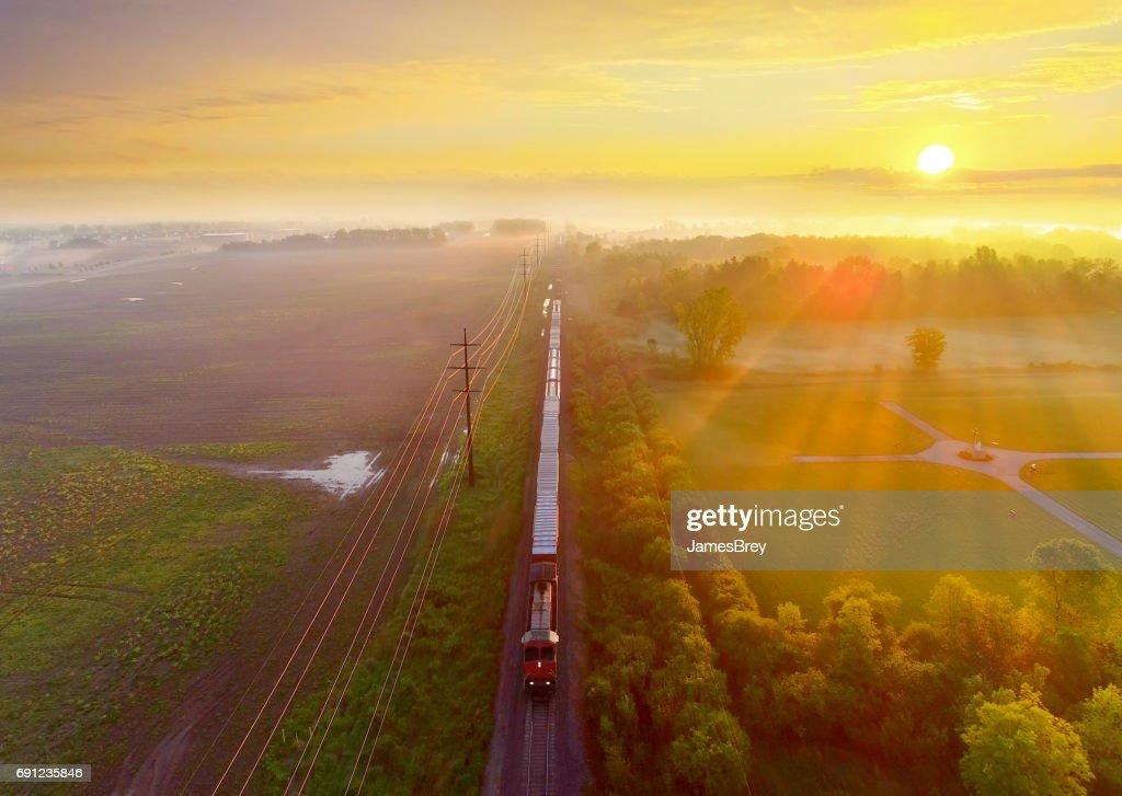 Train rolls through foggy rural landscape at sunrise, aerial view : Stock Photo