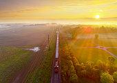 Train rolls through foggy rural landscape at sunrise, aerial view