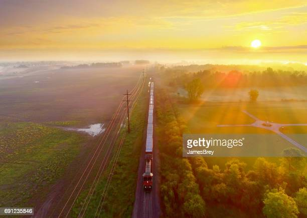 Train rolls through foggy rural landscape at sunrise, aerial view