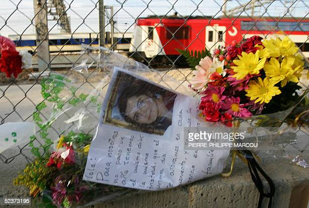 A train runs near Tellez Street in madrid where people have placed flowers candles and pictures in memory of the victims of the 11 March 2004 train...