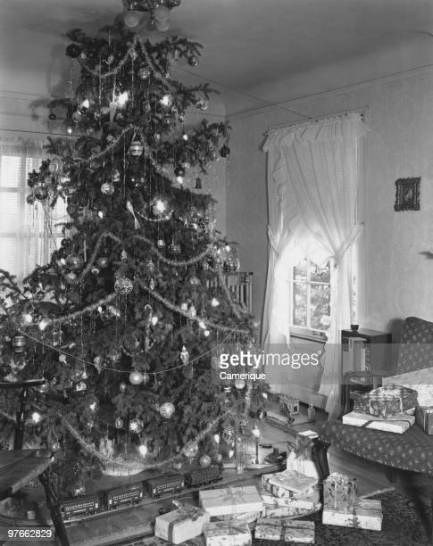 A train set and giftwrapped presents under a large Christmas tree circa 1955