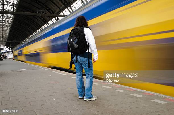 Train speeding by standing woman