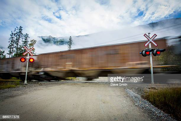 train speeding through railroad crossing - railroad crossing stock pictures, royalty-free photos & images