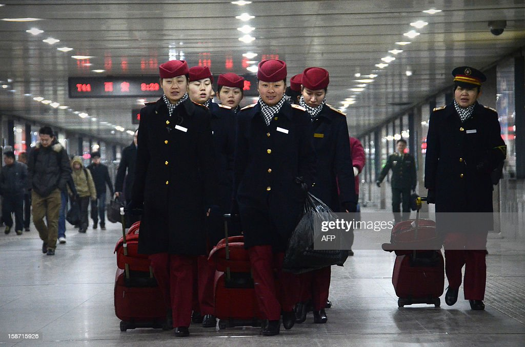 Train stewardesses make their way at the Beijing west railway station in Beijing on December 26, 2012. China on December 26 started service on the world's longest high-speed rail route, the latest milestone in the country's rapid and sometimes troubled super fast rail network.