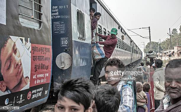 Train stop with billboard on train of ill boy laying in hospital bed with nose tubes locals stare at the camera PATNA BIHAR INDIA
