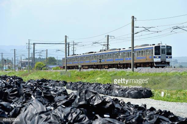 A train takes a test run on the JR Joban Line while bags containing radioactive soil are seen along the railway on May 29 2014 in Naraha Fukushima...