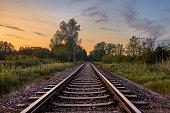 Train tracks infront of beautiful nature and the sunset in Rastatt, Germany
