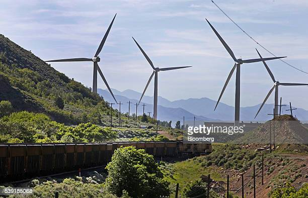 Train transporting coal moves past wind turbines in Spanish Fork, Utah, U.S., on Friday, June 3, 2016. A sharp movement down in coal prices could...