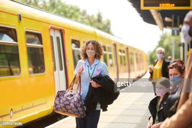 train travel with face masks - essential services stock pictures, royalty-free photos & images