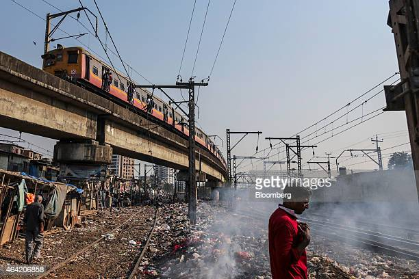 A train travels along an elevated track above shanty houses as trash burns next to ground level tracks near Vadala Road railway station in Mumbai...