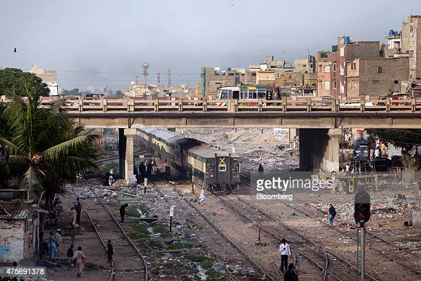 A train travels along rail tracks as traffic passes overhead on a bridge in Karachi Pakistan on Friday May 29 2015 Pakistan's budget is scheduled to...