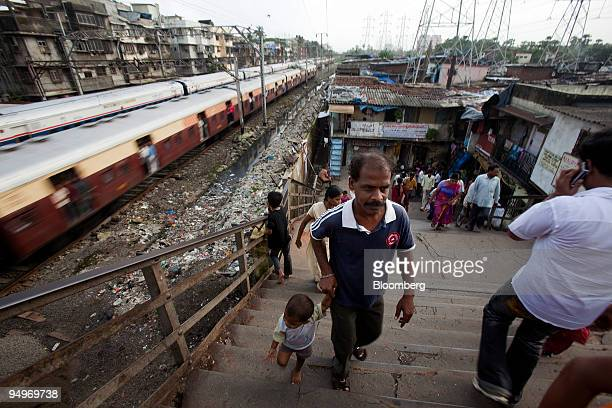 A train travels down the track next to the Dharavi slum area of Mumbai India on Saturday July 2009 Of the 19 million people who reside in Mumbai and...