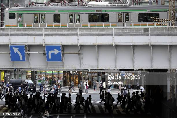 Train travels on an elevated railway track as pedestrians cross a road while in Tokyo, Japan, on Tuesday, July 9, 2019. Japans wages dropped for a...