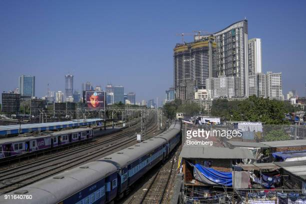 Train travels past slum housing as the under construction Minerva tower, developed by Lokhandwala Infrastructure Pvt., top right, stands in the...