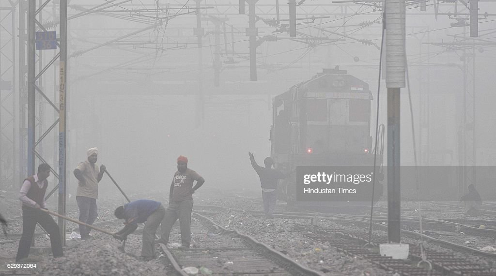 A train travels through dense fog at a railway station on December 12 2016 in Amritsar India Seasonal heavy fog and cold weather disturbed train bus..