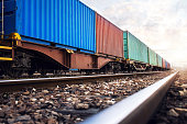 Train wagons carrying cargo containers for shipping companies.