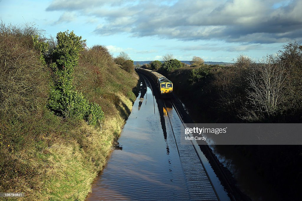 A train waits to pass along flooded track close to the village of North Curry on November 21, 2012 near Taunton, England. Heavy rain overnight has brought widespread disruption to many parts of the UK particularly in the Somerset and Wiltshire and weather forecasters have warned of more wet and windy weather to come.