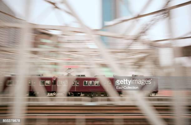 Train with commuters crossing train bridge in Osaka, Japan