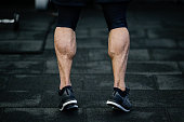 trained legs with muscular calves in sneakers in training gym during hard fitness and gym workout