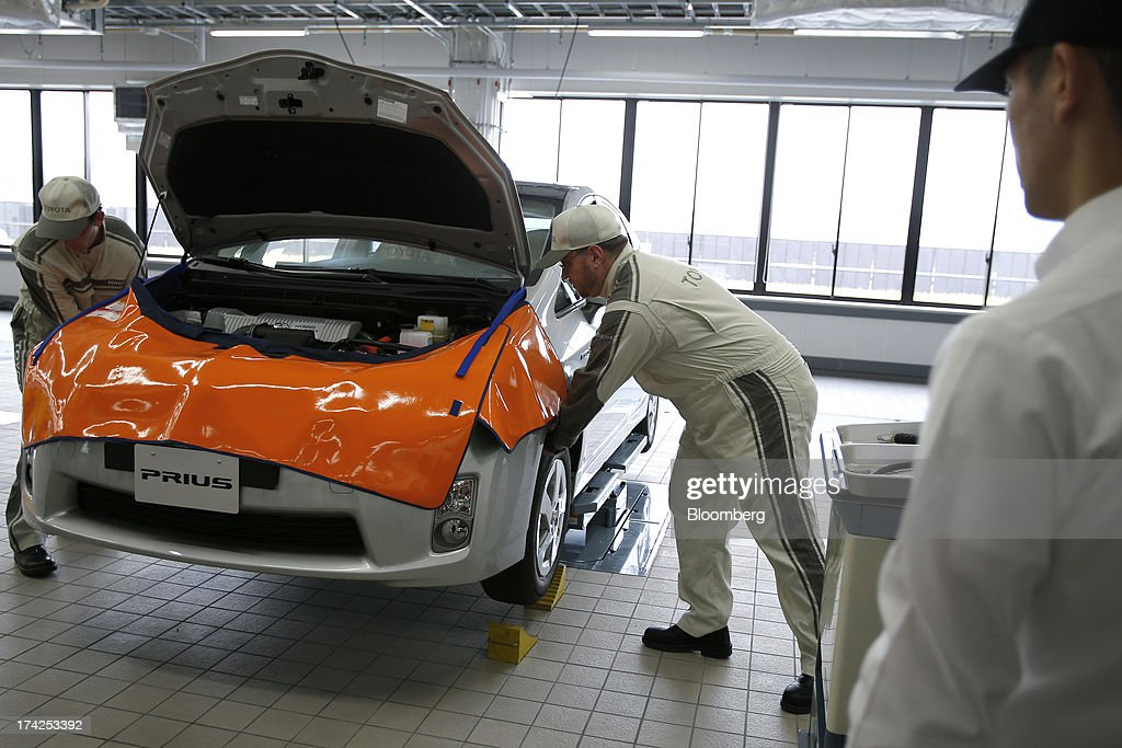 Trainee after-service staff work on a Prius hybrid vehicle as a Toyota Motor Corp. service technical instructor, right, looks on during a maintenance training demonstration at the company's Tajimi service center in Tajimi, Gifu Prefecture, Japan, on Monday, July 22, 2013. Toyota is the world's largest car maker. Photographer: Kiyoshi Ota/Bloomberg via Getty Images