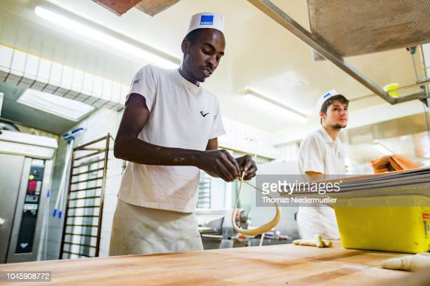 Trainee Anwar Albrnaoy refugee from Nigeria employed at Baeckerei Berger bakery is seen on October 5 2018 in Reutlingen Germany The German government...