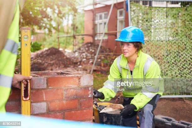 trainee bricklayer listening to her supervisor