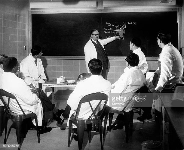 Trainee doctors being given instruction on the blackboard during a lecture 20th April 1959
