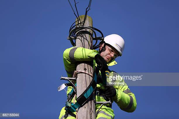 A trainee engineer from BT Openreach a unit of BT Group Plc checks his safety harness at the top of a telegraph pole at the company's training...